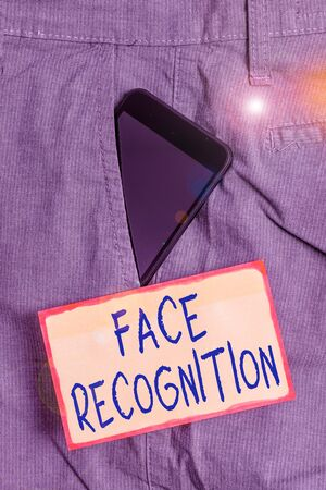 Handwriting text writing Face Recognition. Conceptual photo ability of a computer to scan and recognize huanalysis faces Smartphone device inside formal work trousers front pocket near note paper