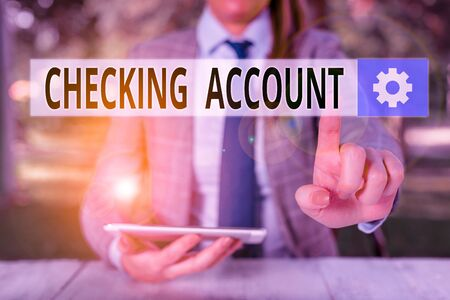 Conceptual hand writing showing Checking Account. Concept meaning bank account that allows you easy access to your money Female business person sitting by table holding mobile phone