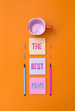 Text sign showing The Best Mom. Business photo text Appreciation for your mother love feelings compliment Coffee cup blank colored sticky note two ballpoints clips yolk background