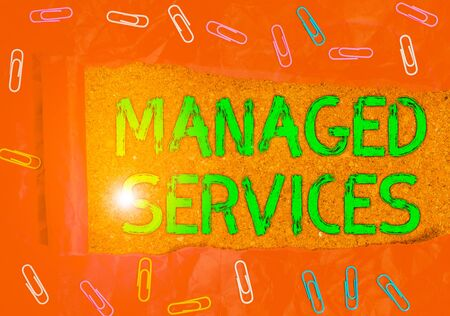 Conceptual hand writing showing Managed Services. Concept meaning company that remotely analysisages customer s is IT infrastructure Paper clip and torn cardboard on wood classic table backdrop
