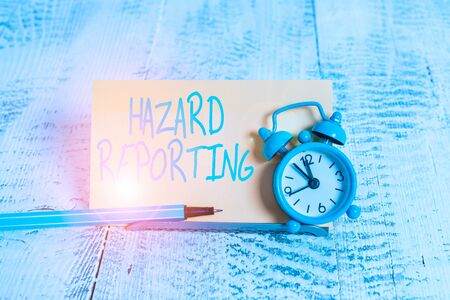 Handwriting text Hazard Reporting. Conceptual photo account or statement describing the danger or risk Mini blue alarm clock stand tilted above buffer wire in front of notepaper Foto de archivo