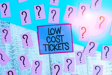 Handwriting text Low Cost Tickets. Conceptual photo small paper bought to provide access to service or show Scribbled and crumbling papers with thick cardboard above wooden table