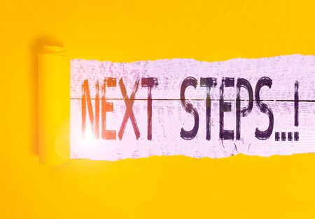 Text sign showing Next Steps. Business photo text something you do after you have finished doing first one Cardboard which is torn in the middle placed above a wooden classic table