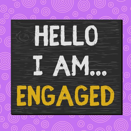 Conceptual hand writing showing Hello I Am... Engaged. Concept meaning He gave the ring We are going to get married Wedding Square rectangle unreal cartoon wood on the coloured wall Фото со стока