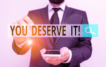Text sign showing You Deserve It. Business photo showcasing should have it because of their qualities or actions Male human wear formal work suit hold smart hi tech smartphone use one hand