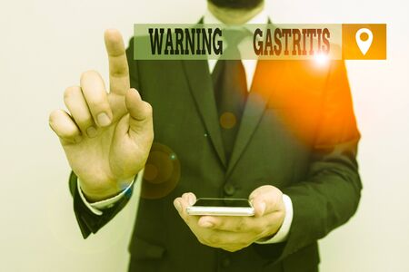 Writing note showing Warning Gastritis. Business concept for early advice on inflammation of the lining of the stomach Male human wear formal work suit hold smartphone using hand