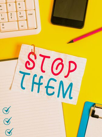 Writing note showing Stop Them. Business concept for used for telling someone not to do something that they are doing Crumpled white paper on table paper clips clock mobile and pc keyboard