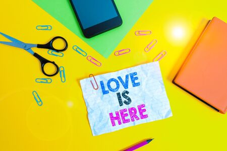Text sign showing Love Is Here. Business photo text Roanalysistic feeling Lovely emotion Positive Expression Care Joy Paper sheets pencil clips smartphone scissors notebook colored background