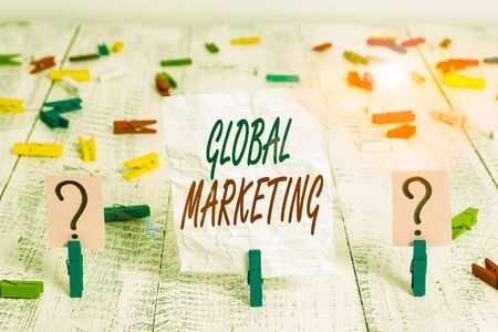 Handwriting text Global Marketing. Conceptual photo firm sells the same products to the global market Scribbled and crumbling sheet with paper clips placed on the wooden table Archivio Fotografico