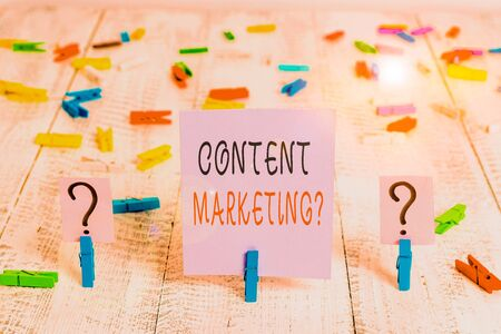 Writing note showing Content Marketing question. Business concept for involves creation and sharing of online material Crumbling sheet with paper clips placed on the wooden table