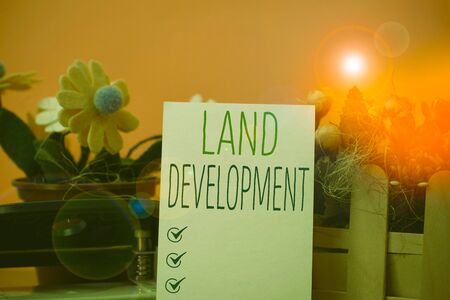 Writing note showing Land Development. Business concept for process of acquiring land for constructing infrastructures Flowers and writing equipments plus plain sheet above textured backdrop Stock Photo