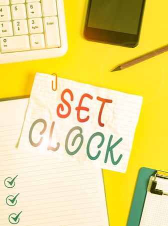 Writing note showing Set Clock. Business concept for put it to the right time or change the clock time to a later time Crumpled white paper on table paper clips clock mobile and pc keyboard