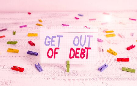 Handwriting text writing Get Out Of Debt. Conceptual photo No prospect of being paid any more and free from debt Green clothespin white wood background colored paper reminder office supply Foto de archivo
