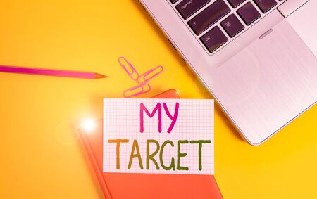 Writing note showing My Target. Business concept for something or someone that you are trying to do or achieve or aimed Laptop clips pencil paper sheet hard cover notebook colored background