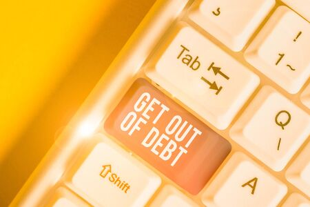 Conceptual hand writing showing Get Out Of Debt. Concept meaning No prospect of being paid any more and free from debt White pc keyboard with note paper above the white background Foto de archivo