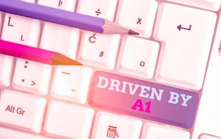 Conceptual hand writing showing Driven By A1. Concept meaning Move or controlled by a top quality driver in the society White pc keyboard with note paper above the white background 스톡 콘텐츠