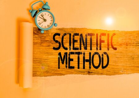 Text sign showing Scientific Method. Business photo showcasing method of procedure that has characterized natural science Alarm clock and torn cardboard placed above a wooden classic table backdrop