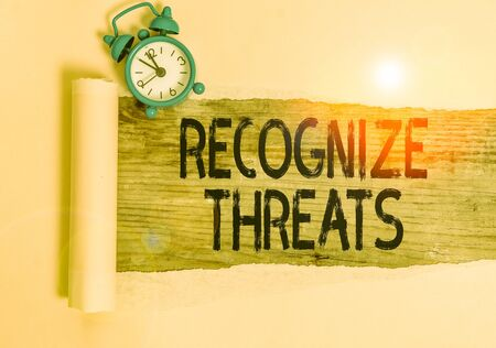 Text sign showing Recognize Threats. Business photo showcasing potential to cause serious harm to a computer system Alarm clock and torn cardboard placed above a wooden classic table backdrop Stockfoto
