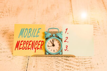 Conceptual hand writing showing Mobile Messenger. Concept meaning mobile tool that allows users to send chat messages Mini blue clock standing above buffer wire between two paper