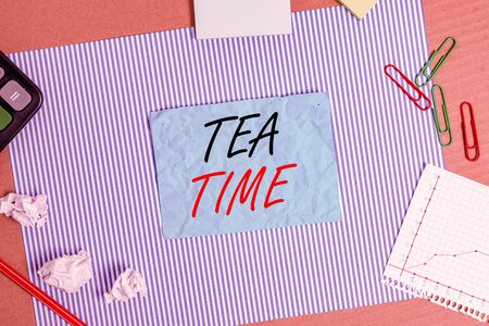 Handwriting text Tea Time. Conceptual photo the time in the afternoon when some showing eat a small meal Striped paperboard notebook cardboard office study supplies chart paper 免版税图像