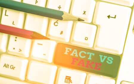 Conceptual hand writing showing Fact Vs Fake. Concept meaning Rivalry or products or information originaly made or imitation White pc keyboard with note paper above the white background 写真素材