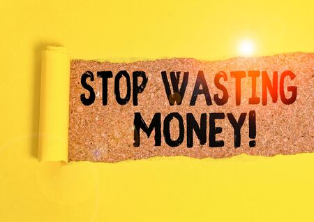 Word writing text Stop Wasting Money. Business photo showcasing advicing demonstrating or group to start saving and use it wisely Cardboard which is torn in the middle placed above a wooden classic table