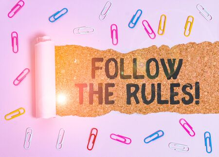 Conceptual hand writing showing Follow The Rules. Concept meaning go with regulations governing conduct or procedure Paper clip and torn cardboard on wood classic table backdrop