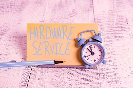 Handwriting text Hardware Service. Conceptual photo act of supporting and maintaining computer hardware Mini blue alarm clock stand tilted above buffer wire in front of notepaper Imagens