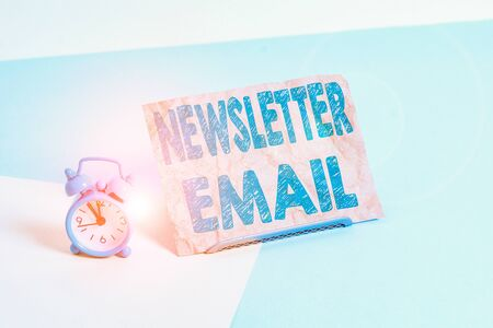 Text sign showing Newsletter Email. Business photo text email sent to subscribers informing them about the news Mini size alarm clock beside a Paper sheet placed tilted on pastel backdrop