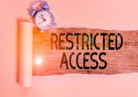 Text sign showing Restricted Access. Business photo showcasing A class of service in which users may be denied access Alarm clock and torn cardboard placed above a wooden classic table backdrop