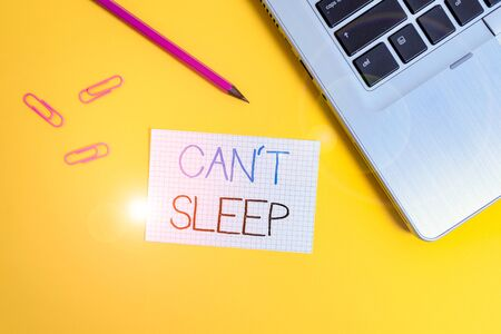 Word writing text Can T Sleep. Business photo showcasing trouble falling asleep or wake up frequently during the night Trendy metallic laptop clips pencil squared paper sheet colored background