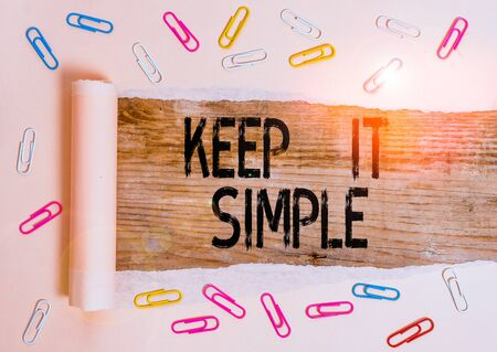 Conceptual hand writing showing Keep It Simple. Concept meaning Remain in the simple place or position not complicated Paper clip and torn cardboard on wood classic table backdrop Imagens
