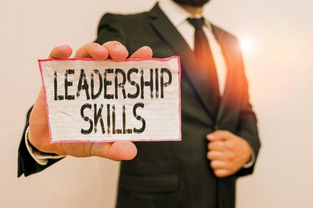Word writing text Leadership Skills. Business photo showcasing Skills and qualities that leaders possess Taking a lead Male human wear formal work suit office look hold notepaper sheet use hand