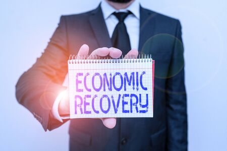Handwriting text writing Economic Recovery. Conceptual photo rise of business activity signaling the end of a recession Male human wear formal work suit office look hold mathematics book use hand