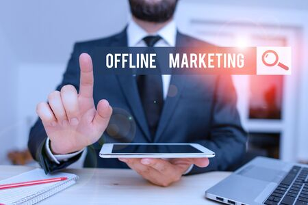 Conceptual hand writing showing Offline Marketing. Concept meaning Advertising strategy published outside of the internet Male human wear formal clothes present use hitech smartphone 스톡 콘텐츠