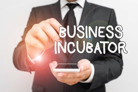 Handwriting text Business Incubator. Conceptual photo company that helps new and startup companies to develop Male human wear formal work suit hold smart hi tech smartphone use one hand