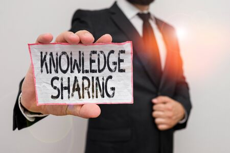 Word writing text Knowledge Sharing. Business photo showcasing deliberate exchange of information that helps with agility Male human wear formal work suit office look hold notepaper sheet use hand 스톡 콘텐츠