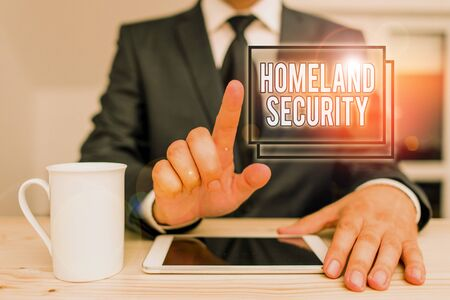 Text sign showing Homeland Security. Business photo text federal agency designed to protect the USA against threats Male human wear formal clothes present presentation use hi tech smartphone Archivio Fotografico