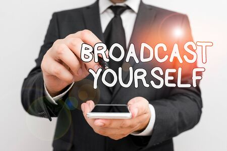 Handwriting text Broadcast Yourself. Conceptual photo broadcasting your viewing interests for all to see Male human wear formal work suit hold smart hi tech smartphone use one hand Stock Photo