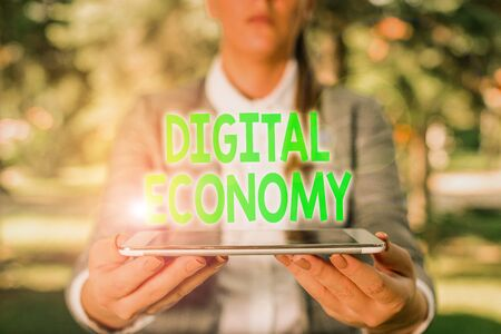 Writing note showing Digital Economy. Business concept for economic activities that are based on digital technologies Outdoor scene with business woman holds lap top with touch screen