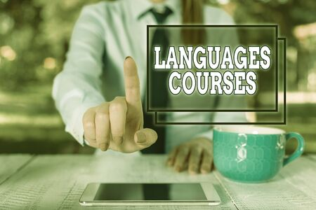 Writing note showing Languages Courses. Business concept for set of classes or a plan of study on a foreign language Business woman sitting by the table with cup of coffee and mobile phone Stockfoto