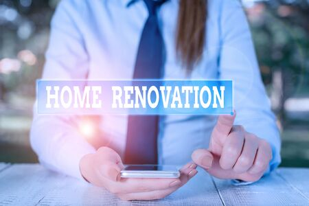 Handwriting text Home Renovation. Conceptual photo process of renovating or making additions to one home Female business person sitting by table and holding mobile phone Foto de archivo