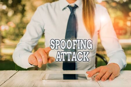 Conceptual hand writing showing Spoofing Attack. Concept meaning impersonation of a user, device or client on the Internet Female business person sitting by table and holding mobile phone