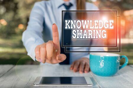 Writing note showing Knowledge Sharing. Business concept for deliberate exchange of information that helps with agility Business woman sitting by the table with cup of coffee and mobile phone