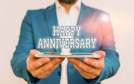 Text sign showing Happy Anniversary. Business photo text The annually recurring date of a past event celebration Businessman holds laptop in his hand. Man holding mobile phone with touch screen