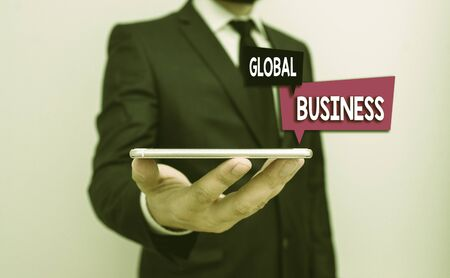 Writing note showing Global Business. Business concept for company that operates facilities in many countries Male human wear formal work suit hold smartphone using hand Banco de Imagens