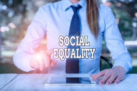 Conceptual hand writing showing Social Equality. Concept meaning applies concerns of justice and fairness to social policy Female business person sitting by table and holding mobile phone
