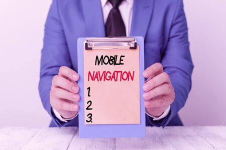 Writing note showing Mobile Navigation. Business concept for graphical user interface used to aid the vehicle driver Man holds empty paper with copy space in front of him Space 스톡 콘텐츠