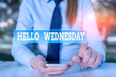 Handwriting text Hello Wednesday. Conceptual photo Hump day Middle of the working week of the calendar Female business person sitting by table and holding mobile phone