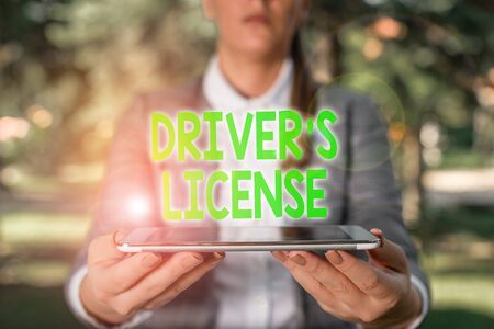 Writing note showing Driver S License. Business concept for a document permitting a demonstrating to drive a motor vehicle Outdoor scene with business woman holds lap top with touch screen